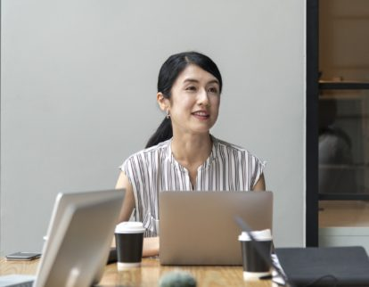 Local business woman sits at meeting room table in front of laptop